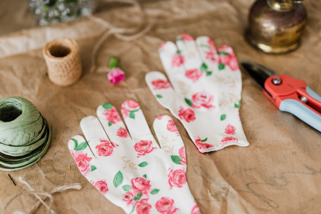 garden gloves with floral print together with pruner and twine